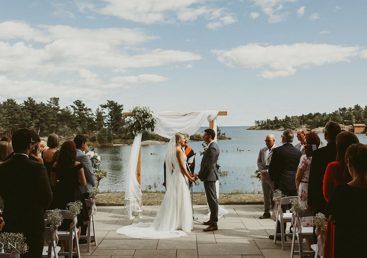 Bride and groom overlooking water at ceremony