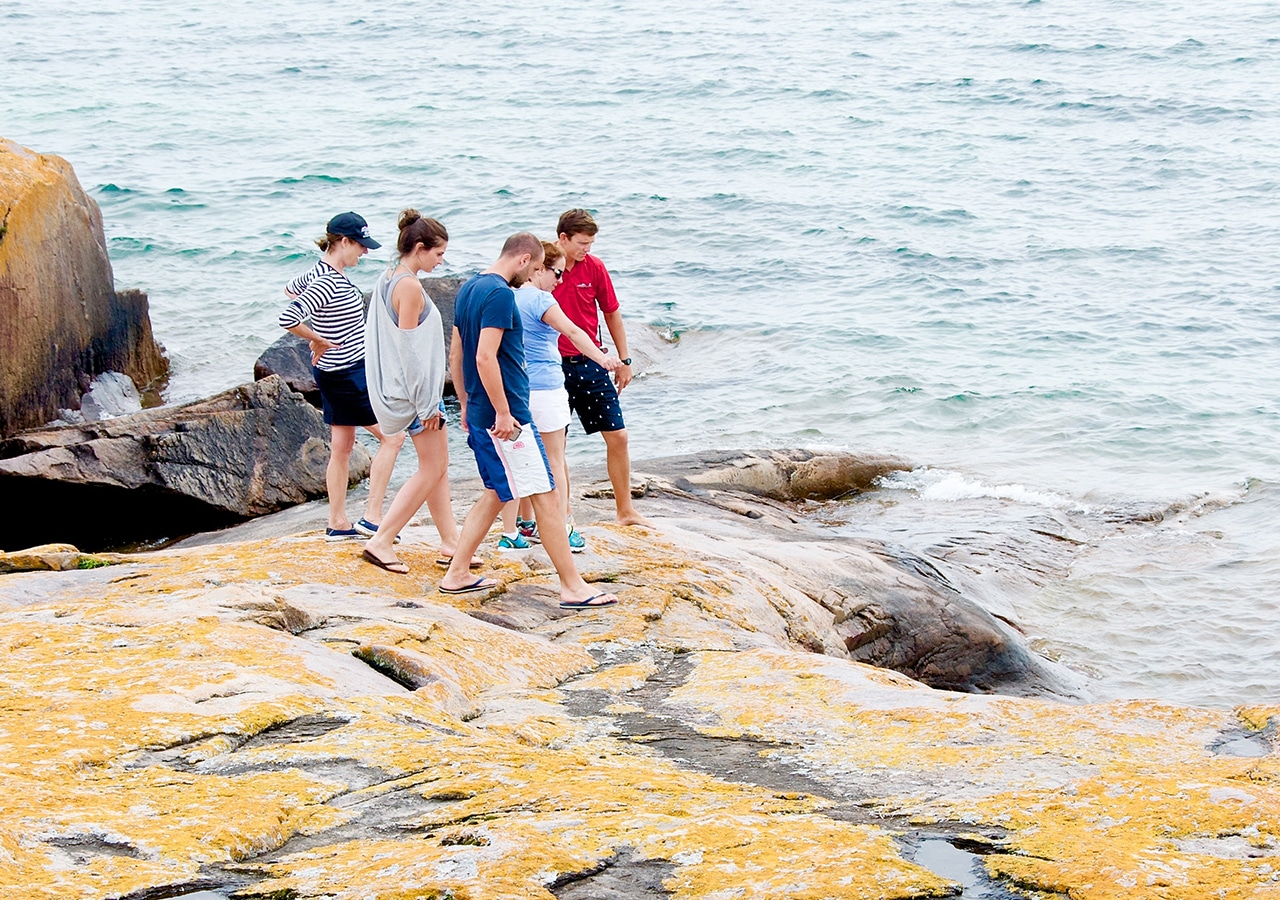 Friends exploring rocks by water